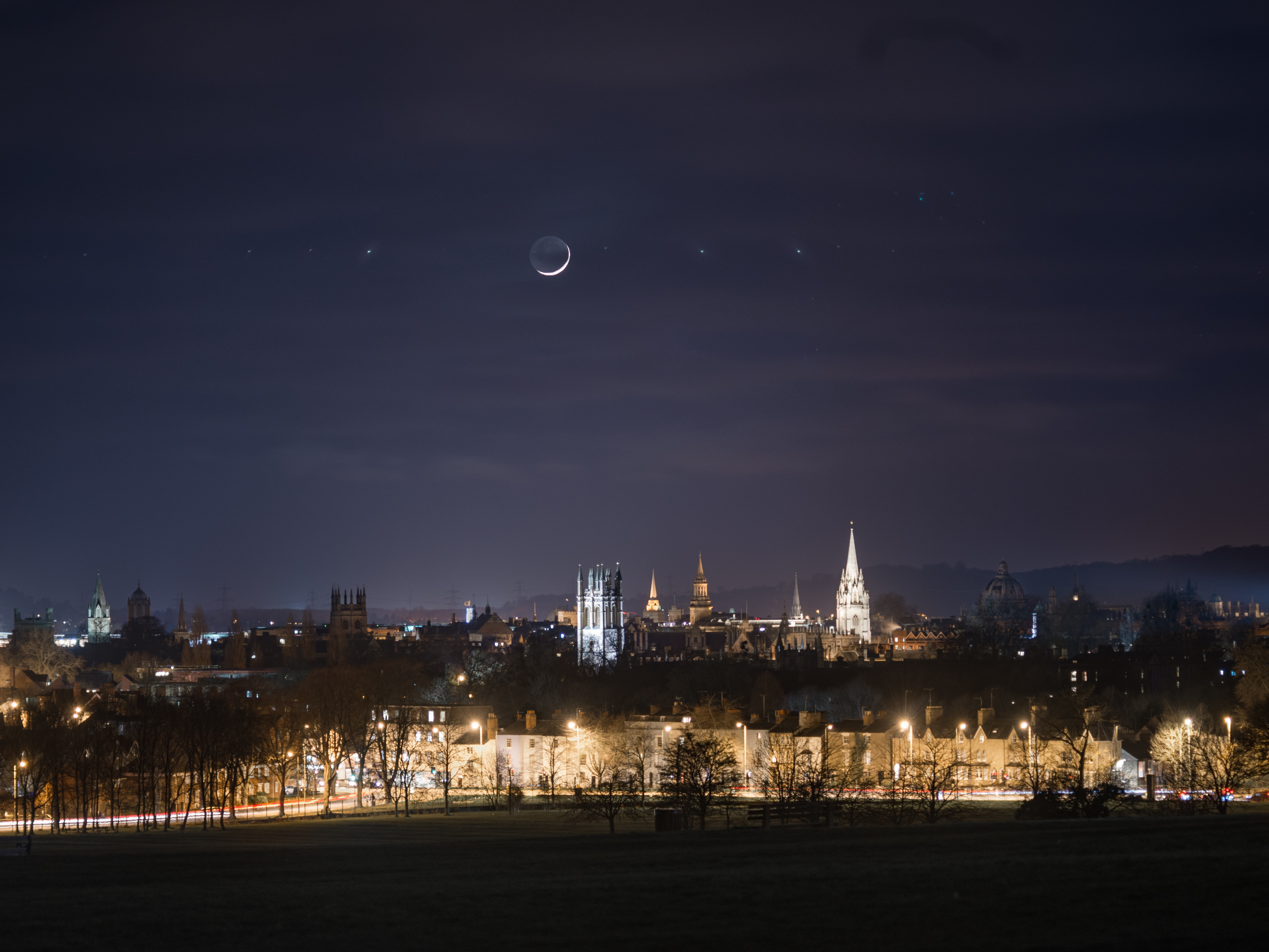 View of Oxford at night showing a new moon above the Dreaming Spires